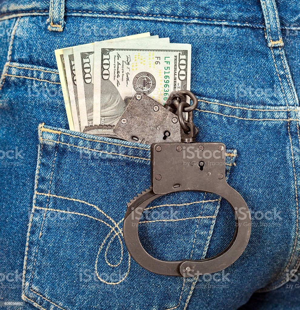 Black metal handcuffs and american currency in back jeans pocket stock photo