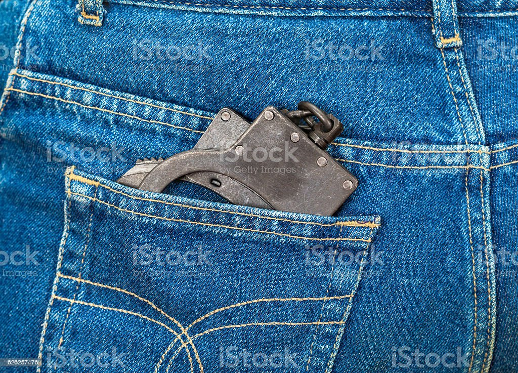 Black metal handcuffs in back jeans pocket stock photo