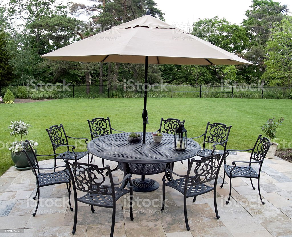 Black metal patio furniture set with tan umbrella stock photo