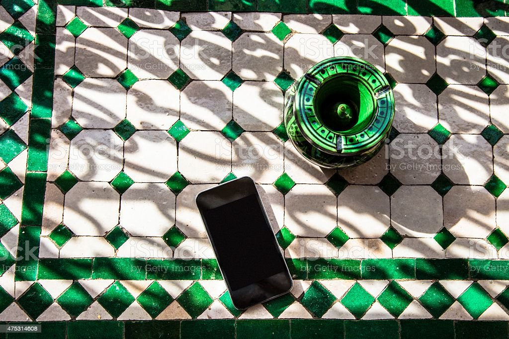 Black mobile phone laying on decorated moroccan table stock photo