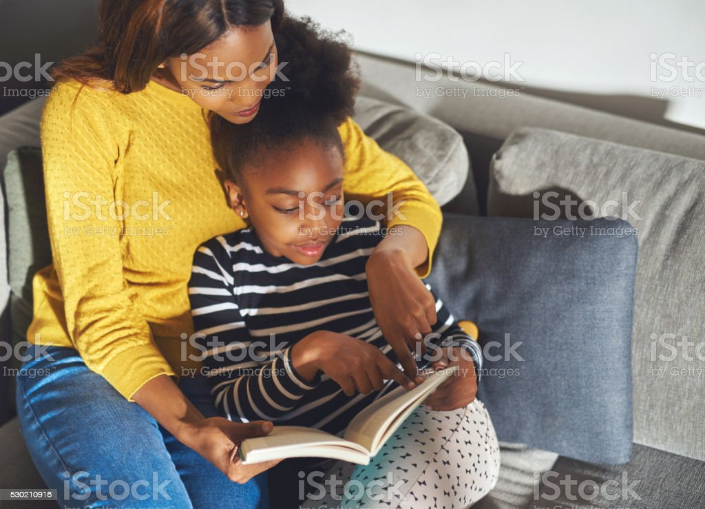 Black mom learning daughter to read stock photo