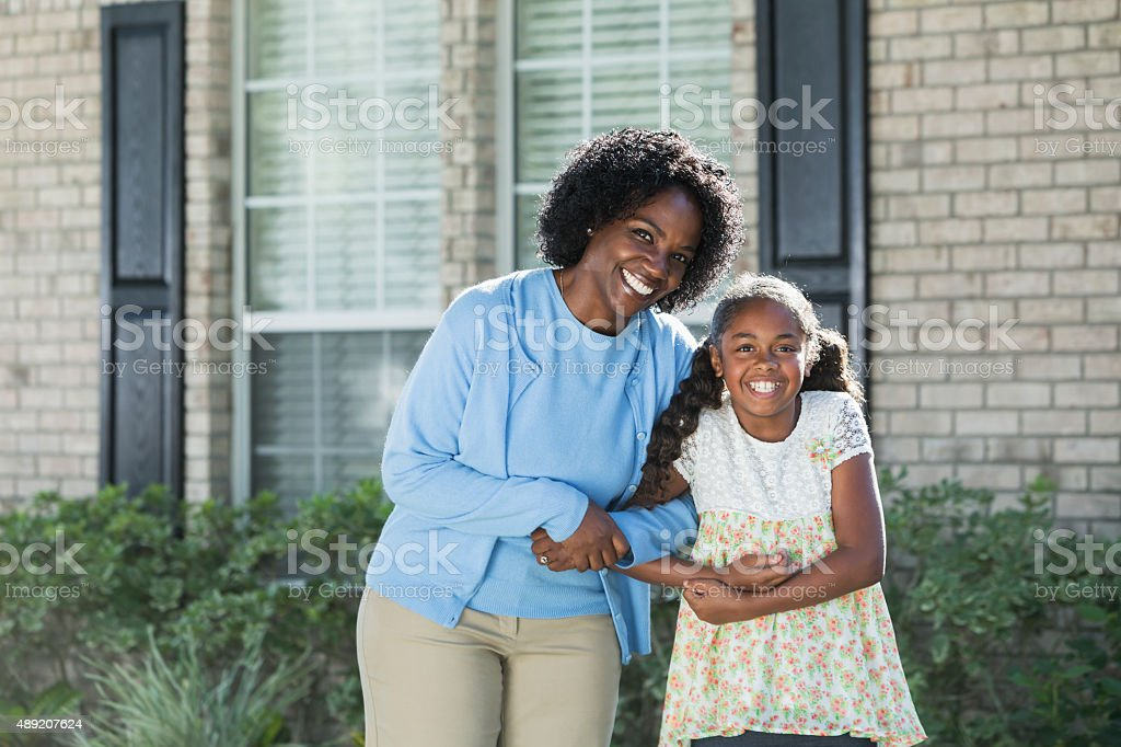 Black mother and daughter outside home stock photo