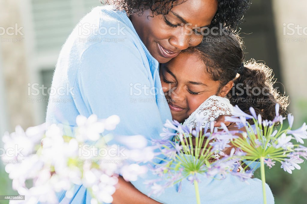 Black mother hugging daughter outdoors with flowers stock photo