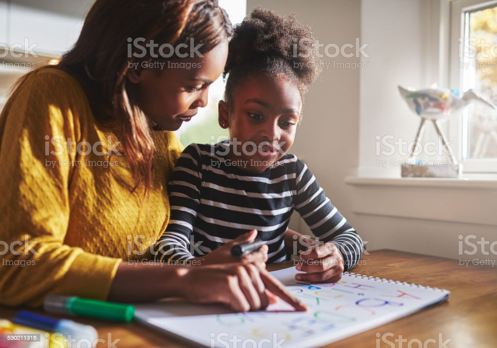 Black mother learning her daughter the alphabet stock photo
