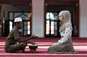 Black Muslim man and woman praying in mosque