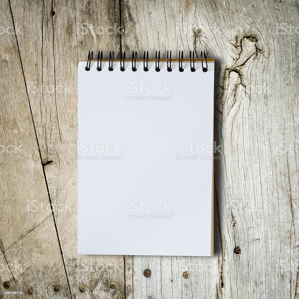 Black notebook on a wood background with clipping path stock photo