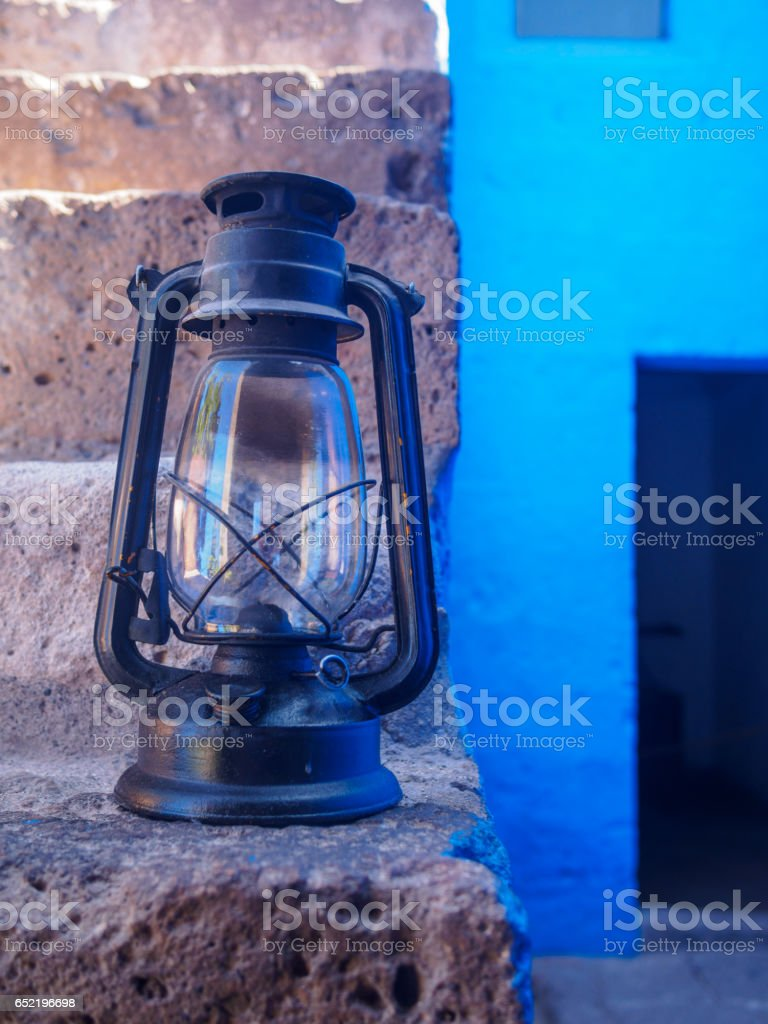 Black oil lamp on stone staircase, with blue blackground stock photo