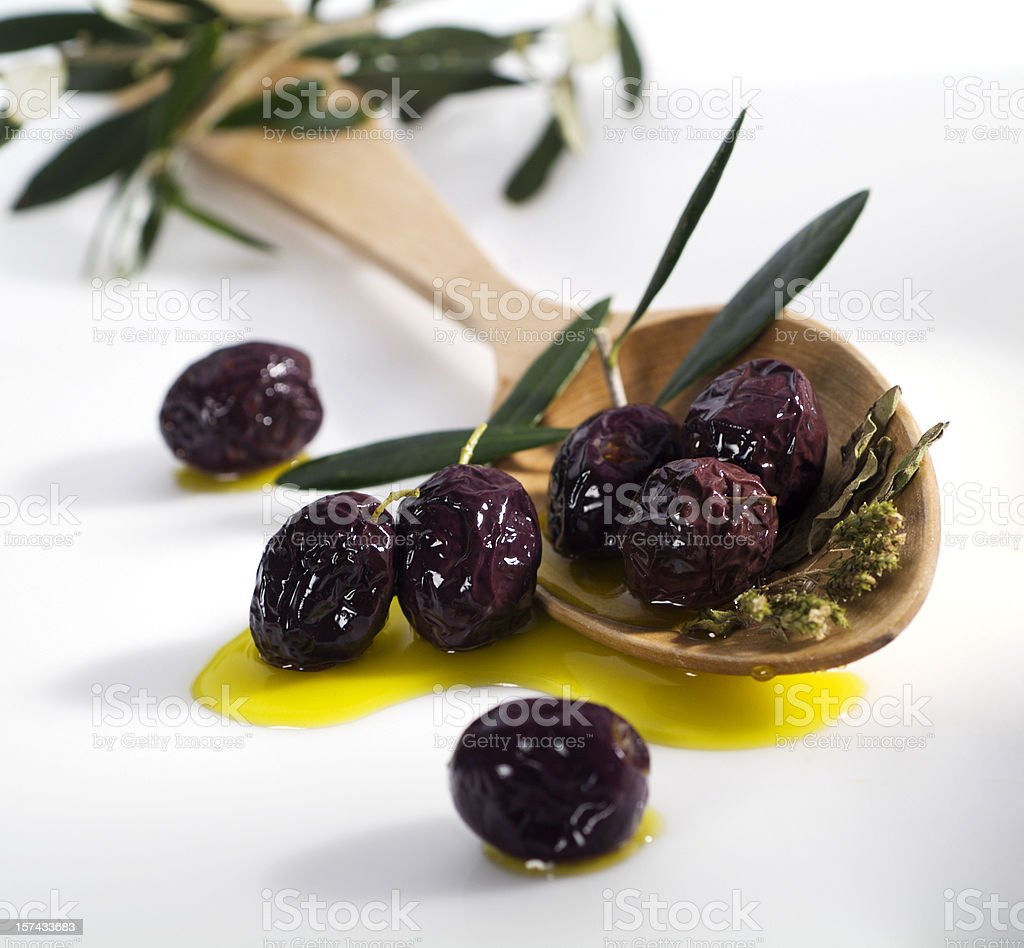Black olives and a wooden ladle royalty-free stock photo