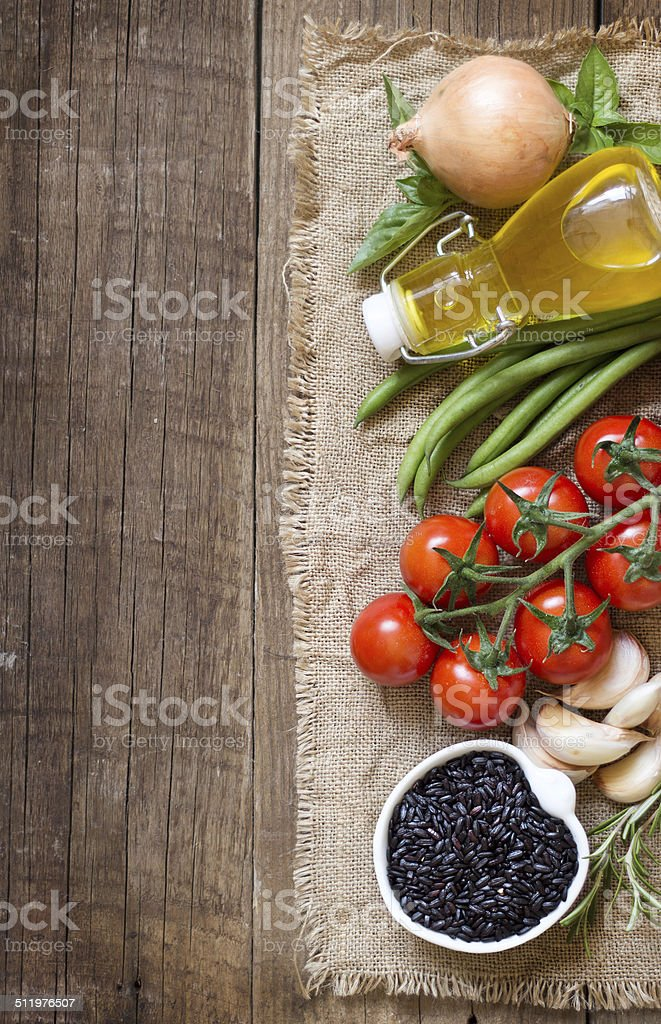 Black organic rice, olive oil, vegetables and herbs stock photo