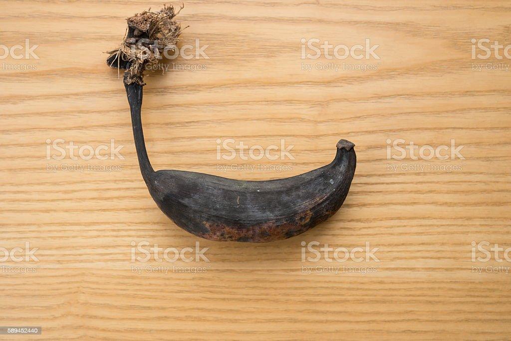 black overripe banana on a wooden table stock photo