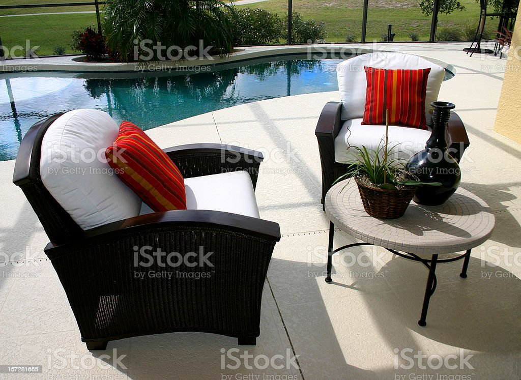 Black, padded patio chairs with red pillows by a pool stock photo