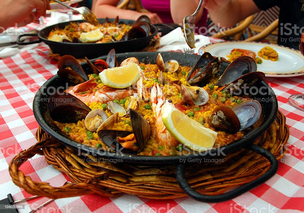 A black pan of paella on a checkered tablecloth stock photo