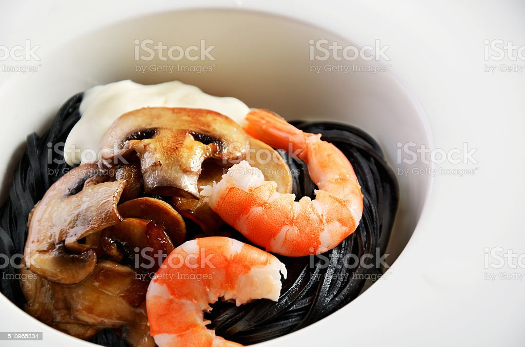 black pasta with shrimp, mushrooms and bechamel sauce in white stock photo