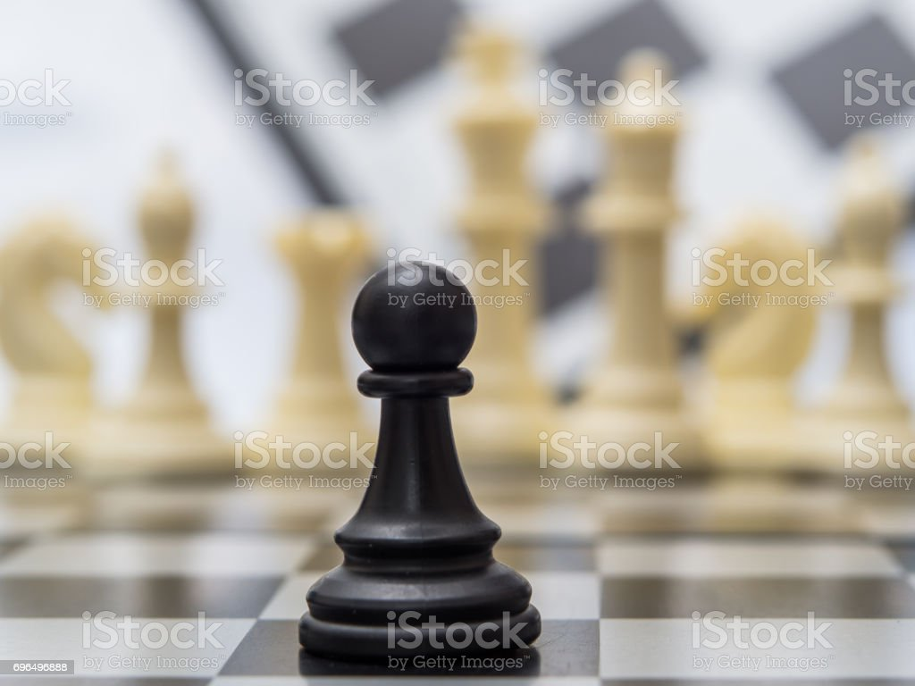 black pawn against the background of white chess pieces stock photo