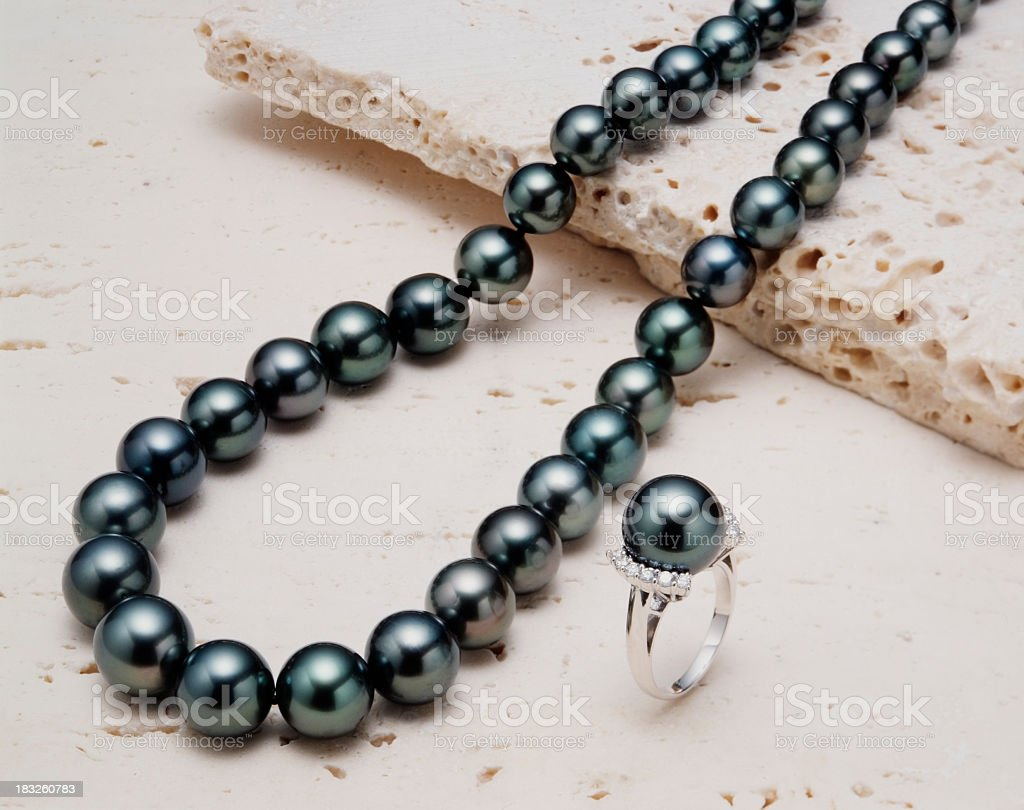 Black pearl necklace with ring on white stone royalty-free stock photo