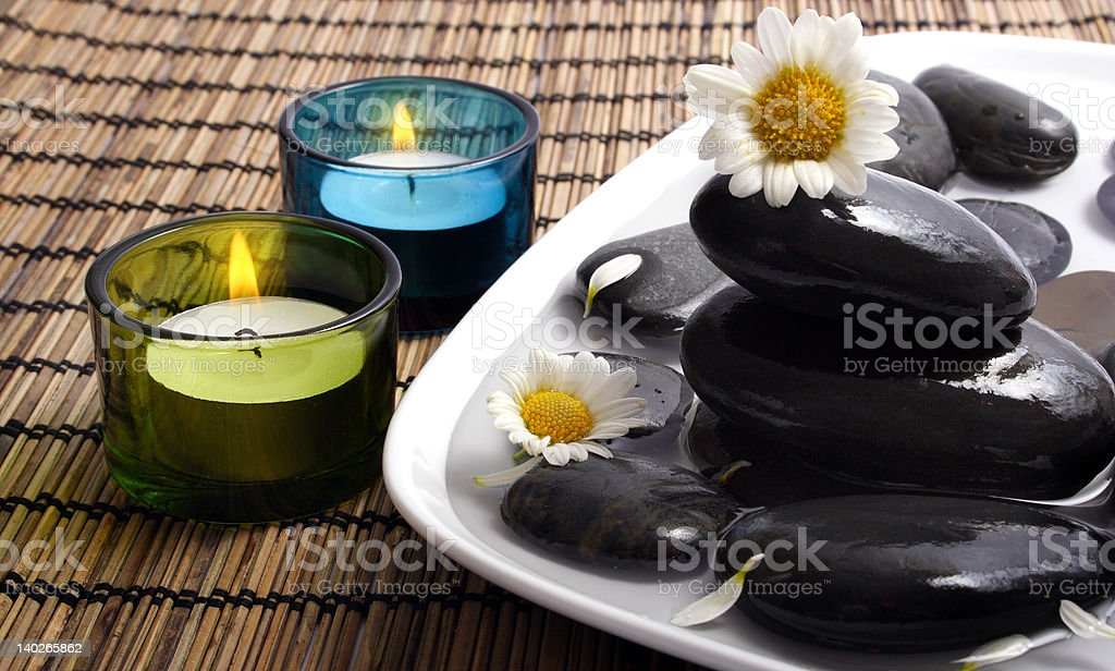 Black pebbles and daisies in water royalty-free stock photo