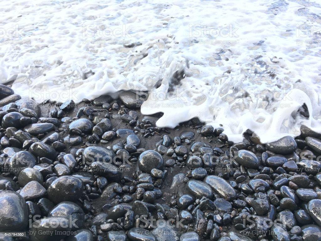 Black pebbles on black sand beach stock photo