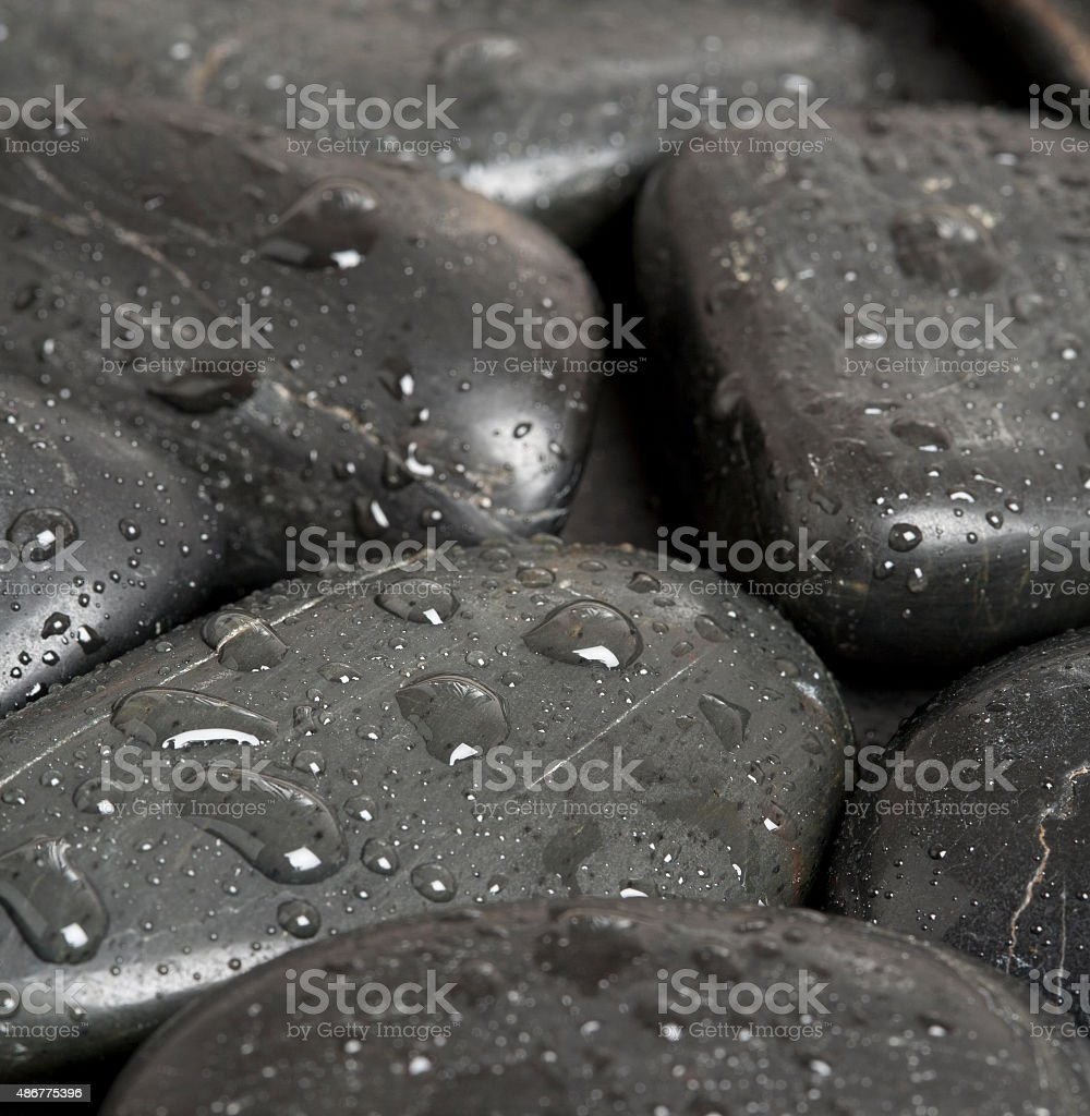 Black pebbles with waterdrops stock photo