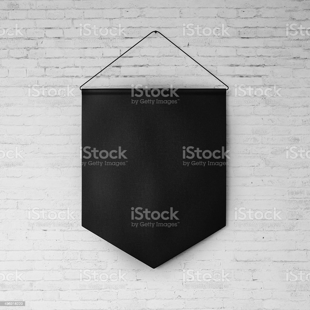 Black pennant hanging on the white bricks wall at background stock photo