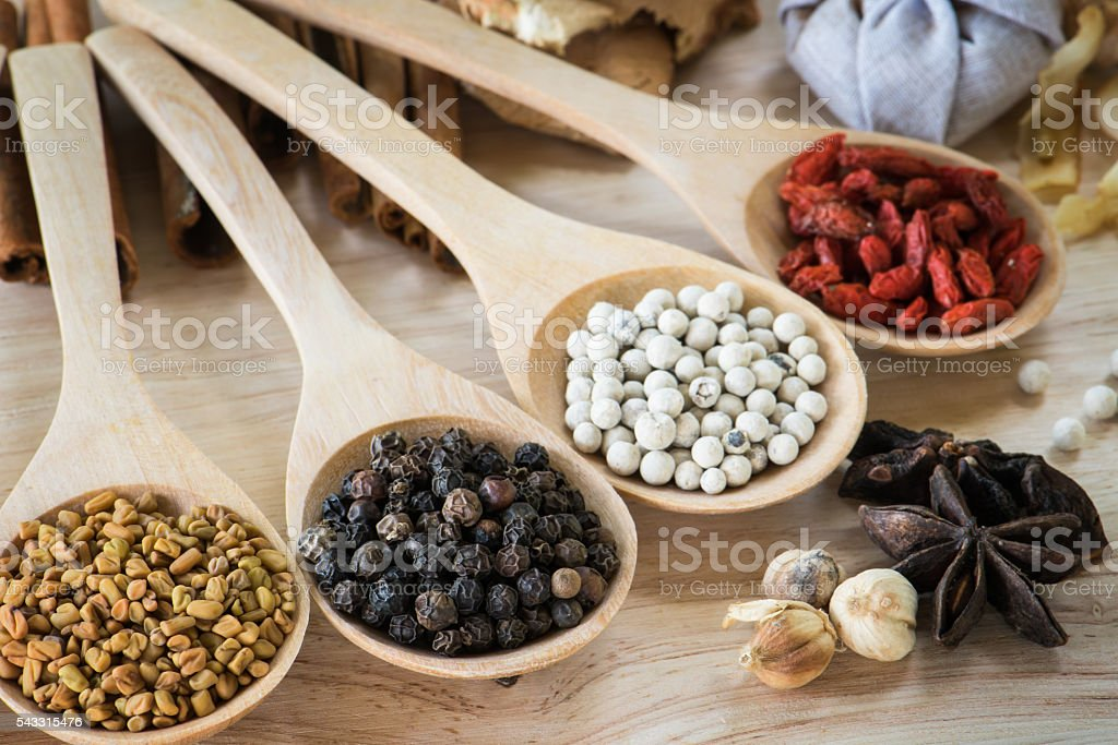 Black pepper in wooden spoon with different ingredient stock photo
