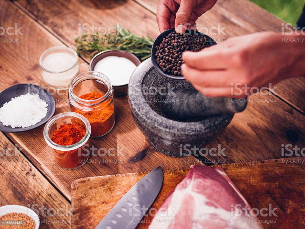 Black peppercorns being put into a mortar and pestle stock photo