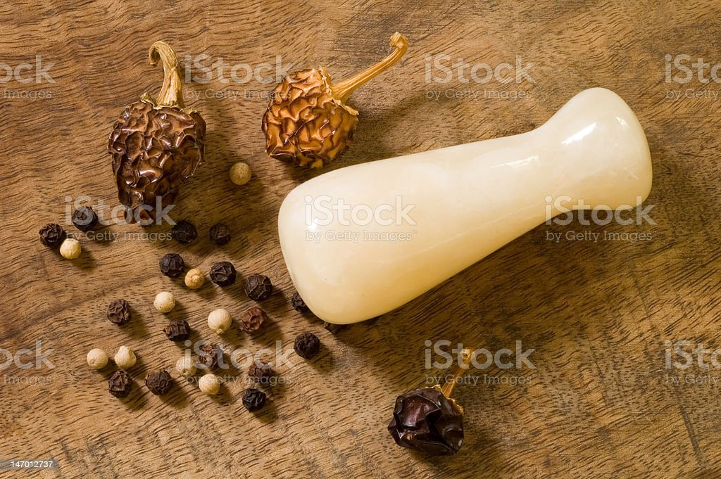 Black peppercorns, dried red peppers and a pestle royalty-free stock photo