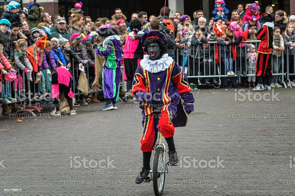 Black Pete is cycling after Sinterklaas arrived stock photo
