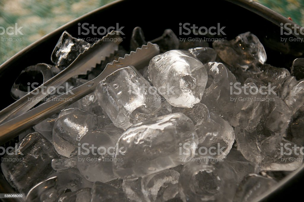 Black plastic ice bucket and stainless steel ice tongs stock photo