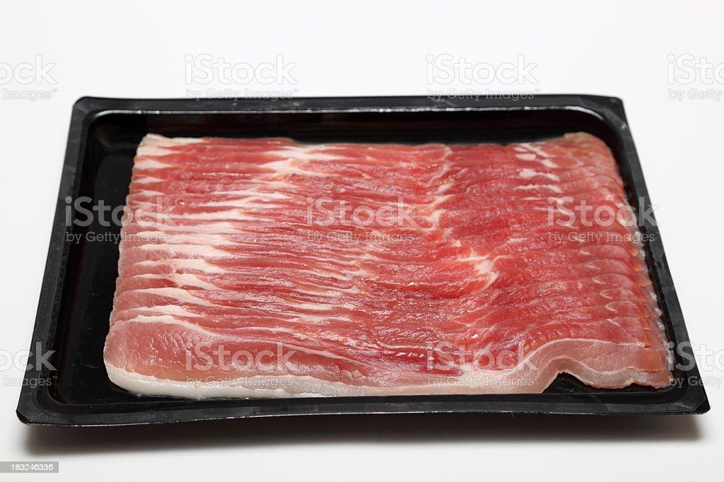 black plastic pack of streaky bacon on plain background stock photo