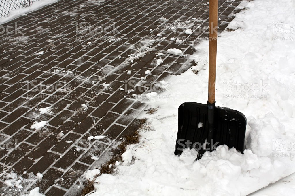 Black plastic snow shovel and pavement. stock photo
