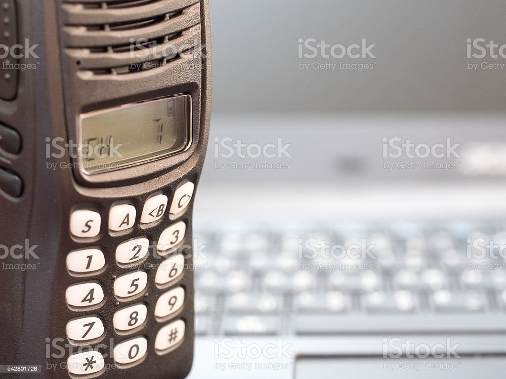black portable radio communication with blurred keyboard in background. stock photo