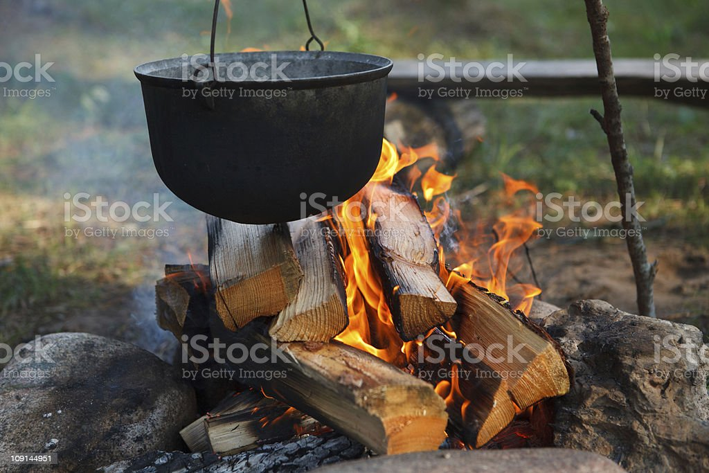 A black pot full of food cooking over campfire stock photo