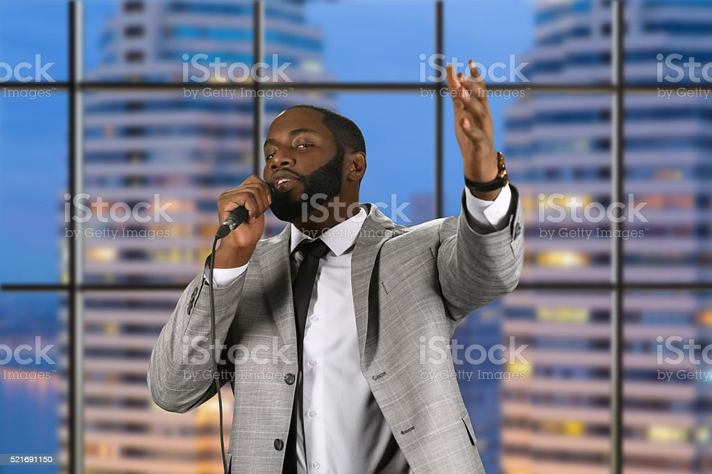 Black preacher speaking into microphone. stock photo