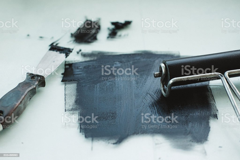 Black printmaking ink with roller and spatula stock photo
