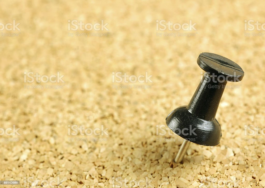 Black push-pin in corkboard royalty-free stock photo