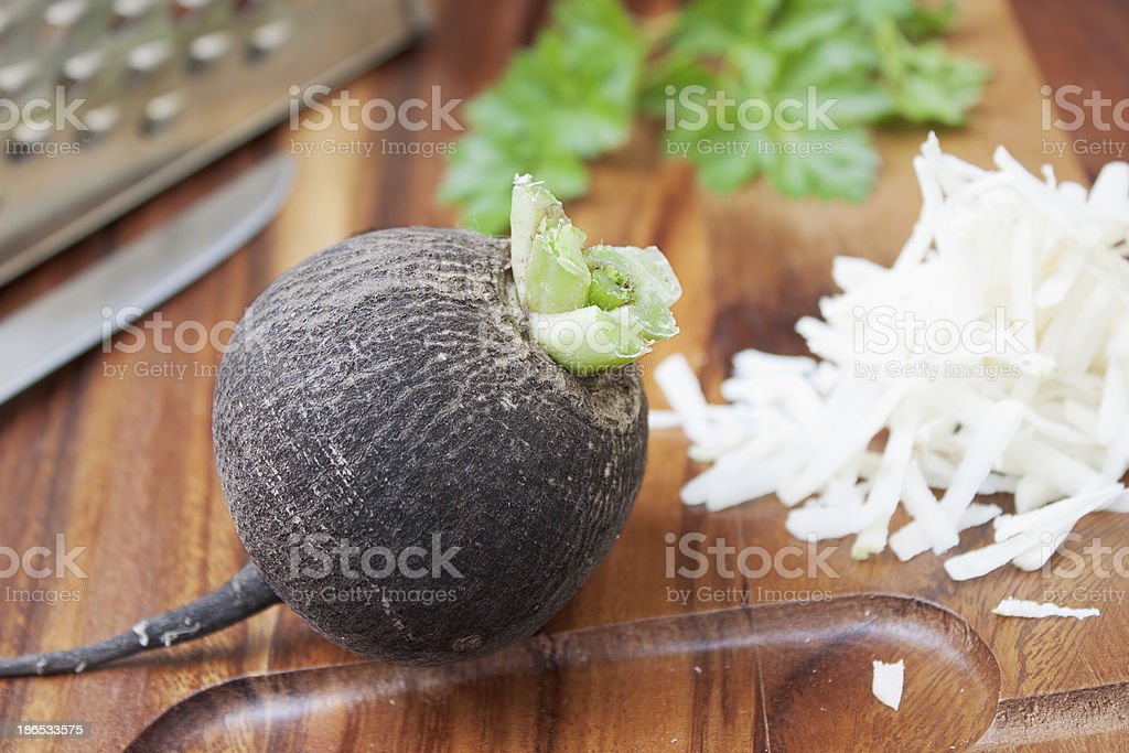 Black radish rub on a small grater royalty-free stock photo