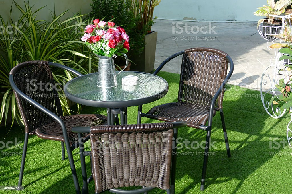 black rattan chair, desk and fake flower in the vase stock photo
