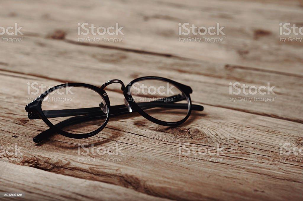 black reading glasses on wooden background stock photo