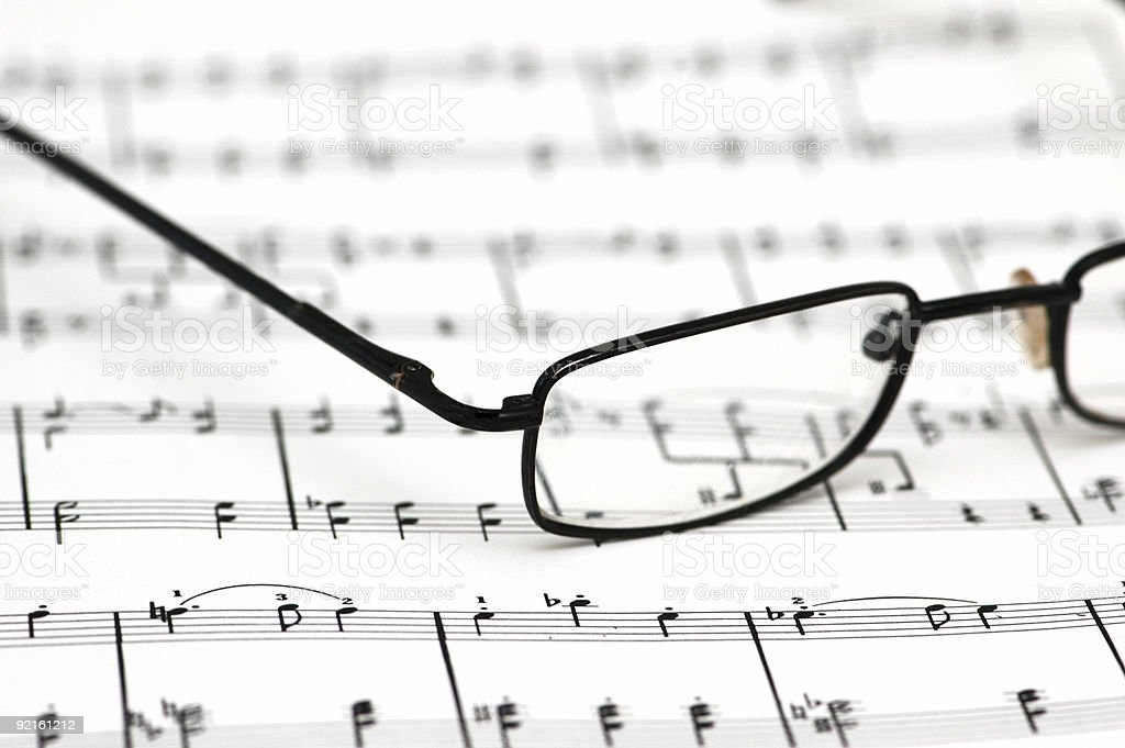Black reading glasses over the music sheets stock photo