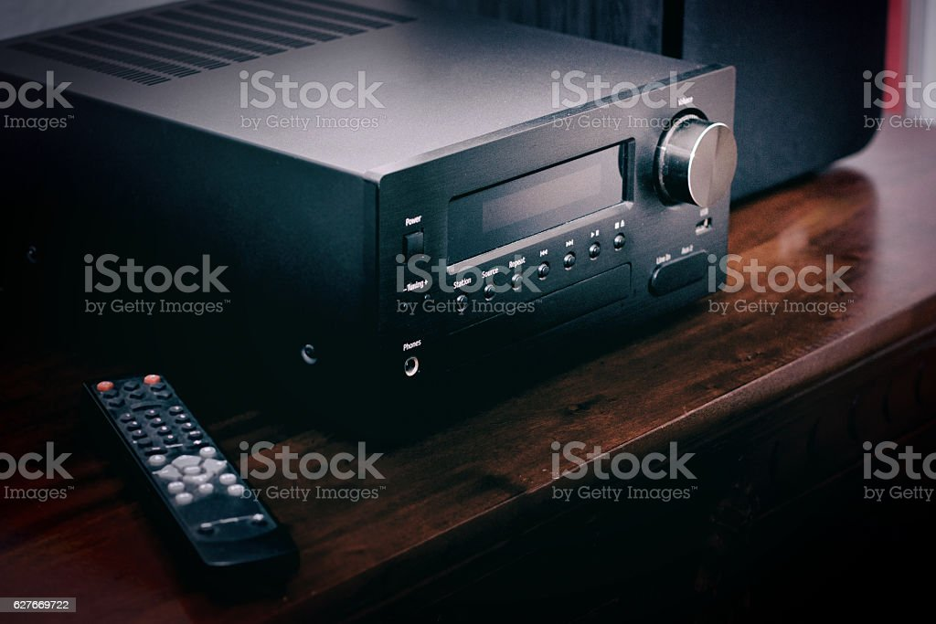Black receiver and remote on wooden desk stock photo