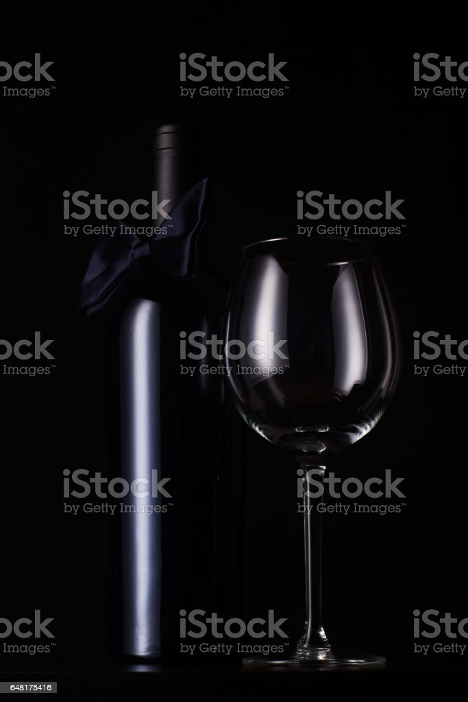black red wine bottle with empty tall glass stock photo