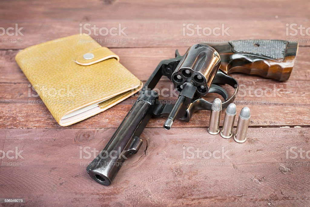 Black revolver gun and and leather bag over stock photo