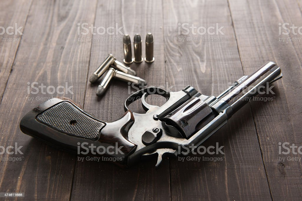 black revolver gun with bullets isolated on wooden background stock photo