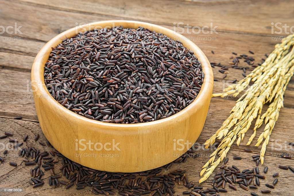 Black rice in bowl on wooden table stock photo