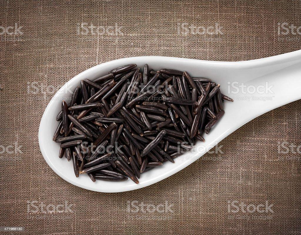Black rice in white porcelain spoon on sackcloth background stock photo