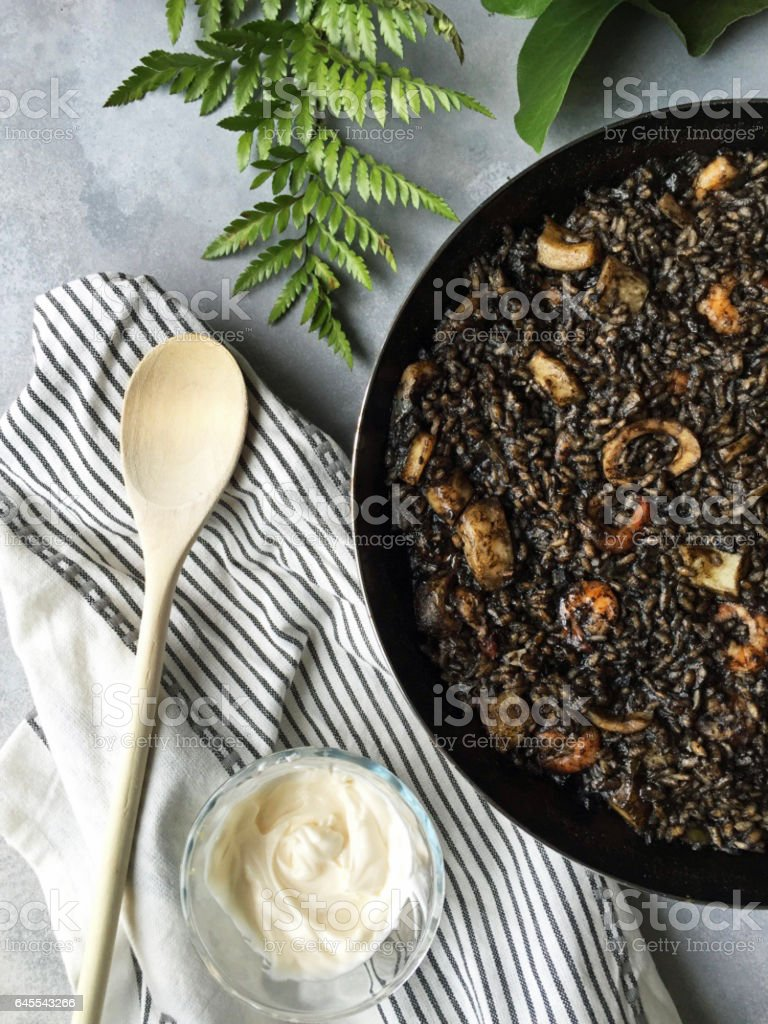 Black Rice Paella in Paellera Pan and allioli Top View stock photo