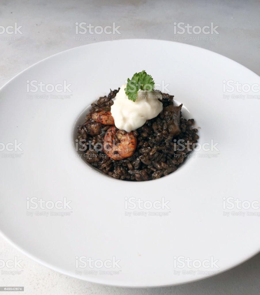 Black Rice Paella on white plate and allioli sauce stock photo