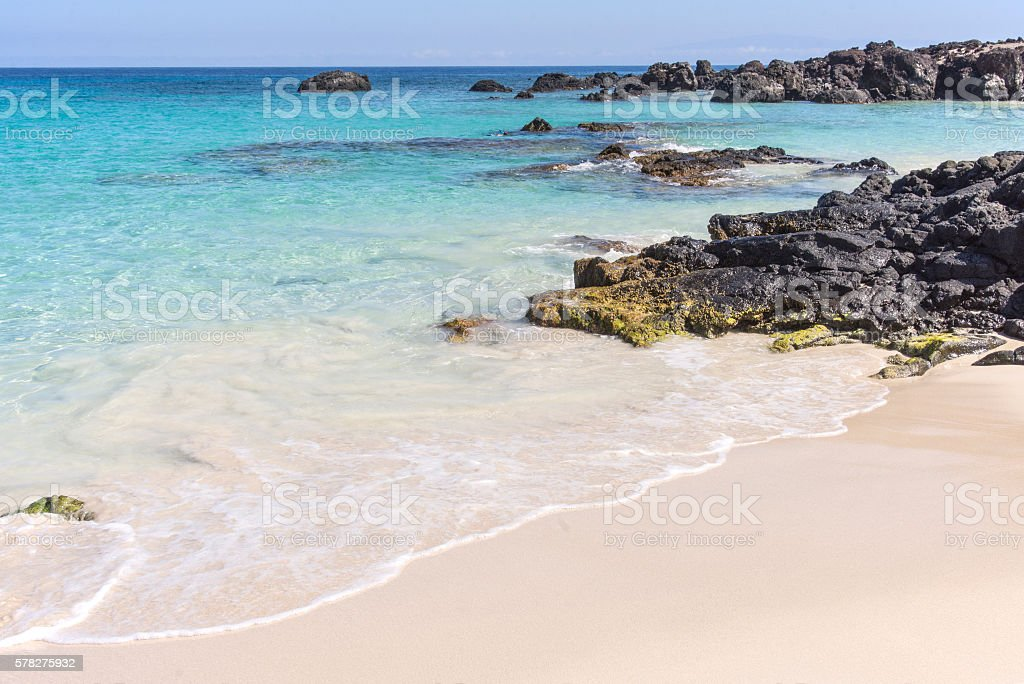 Black rock and turquoise water stock photo
