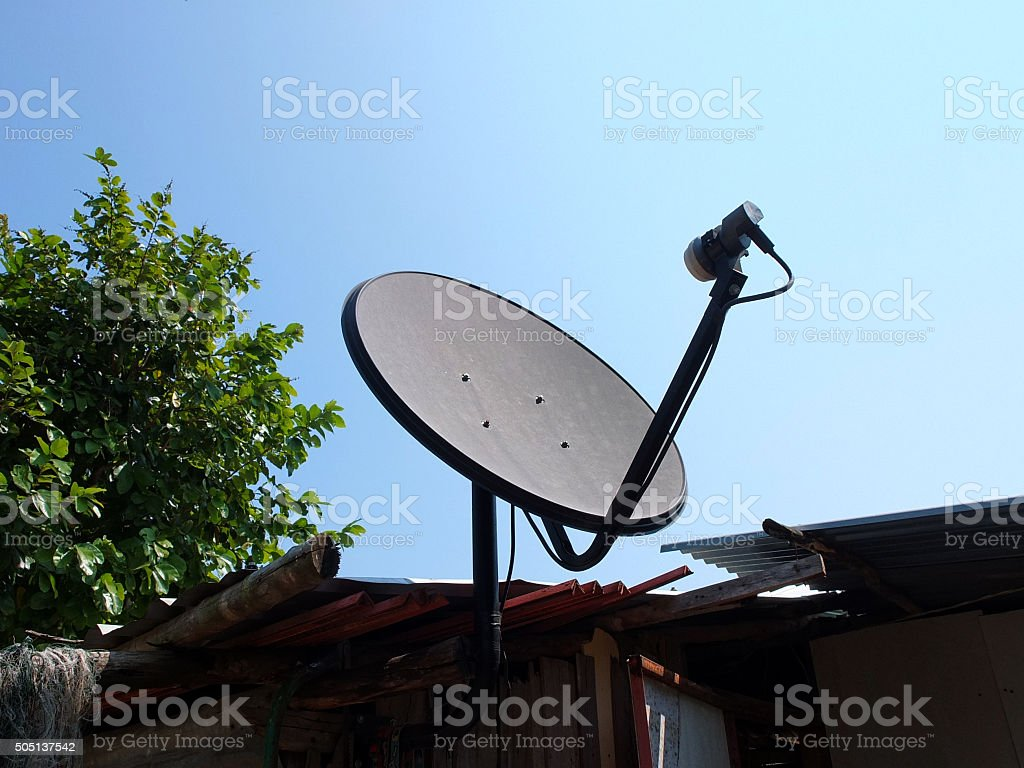Black satellite dish at Old house in the woods stock photo