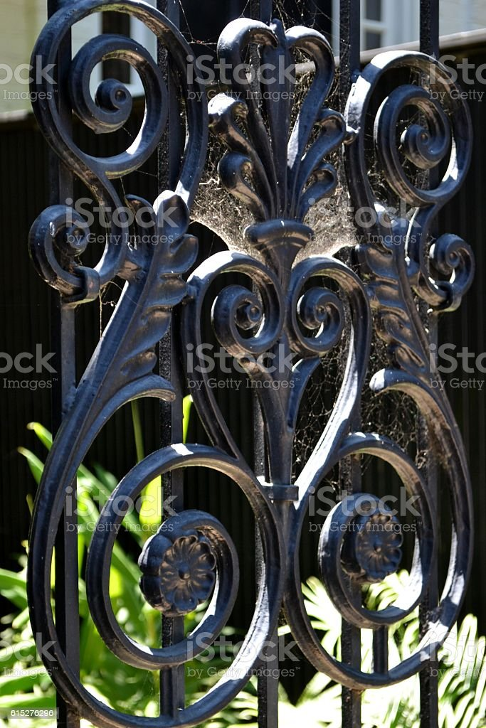 Black Scrolled Wrought Iron Fence With Spider Web royalty-free stock photo